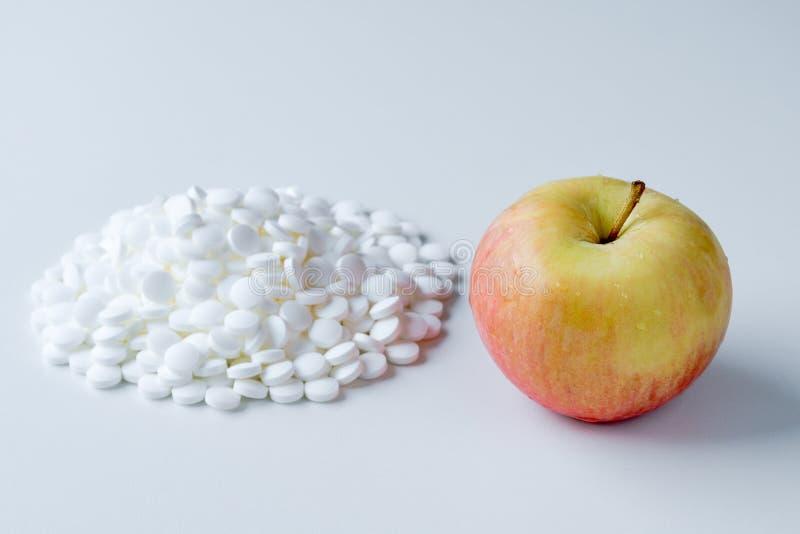Φρέσκο juicy μήλο εναντίον ενός σωρού των χαπιών στοκ φωτογραφία με δικαίωμα ελεύθερης χρήσης