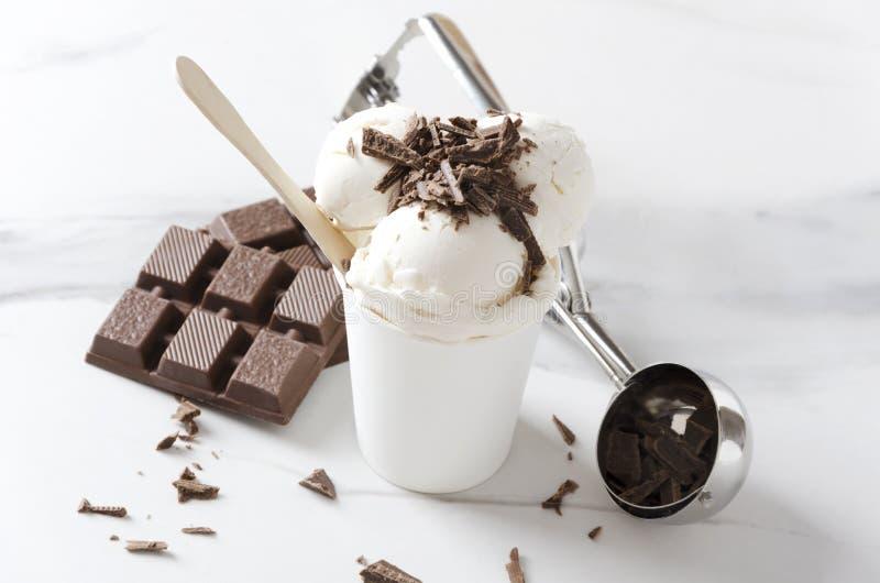 Φρέσκο sundae παγωτού με τη σοκολάτα ψεκάζει στην κορυφή, το φραγμό σοκολάτας και το κουτάλι παγωτού στον άσπρο πίνακα, coseup το στοκ φωτογραφίες με δικαίωμα ελεύθερης χρήσης