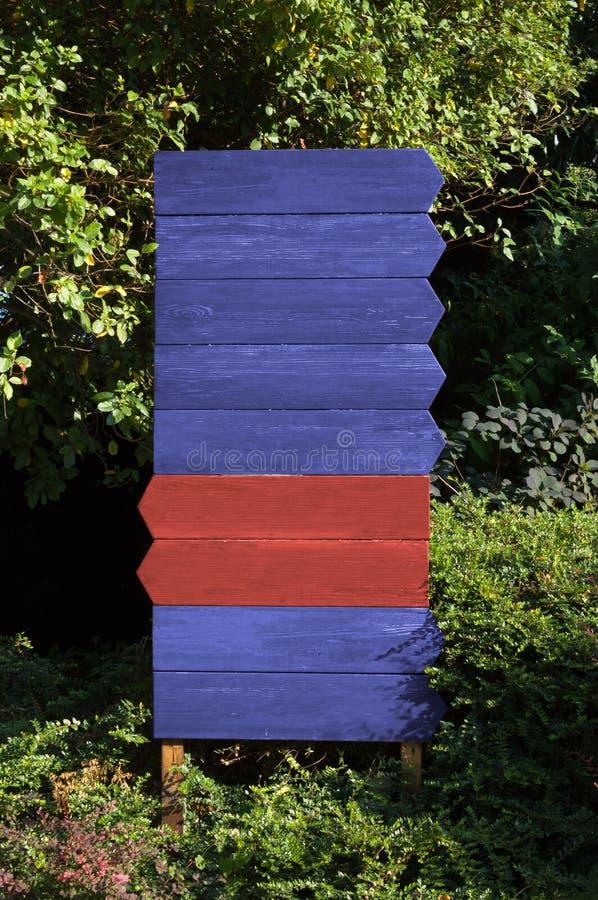 Φραγμός εννέα ξύλινων μπλε και κόκκινων σημαδιών κατευθύνσεων στοκ φωτογραφίες με δικαίωμα ελεύθερης χρήσης