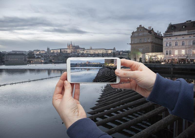 Φυσική άποψη του ιστορικού κέντρου Πράγα, γέφυρα του Charles και κτήρια του παλαιού πόλης χεριού με ένα smartphone, στην οθόνη το στοκ εικόνες