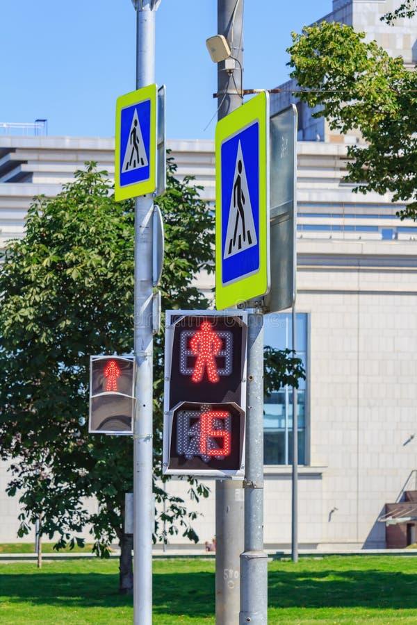 Φωτεινοί σηματοδότες των για τους πεζούς οδηγήσεων με τα οδικά σημάδια της διάβασης πεζών στην οδό στην ηλιόλουστη θερινή ημέρα στοκ φωτογραφία με δικαίωμα ελεύθερης χρήσης