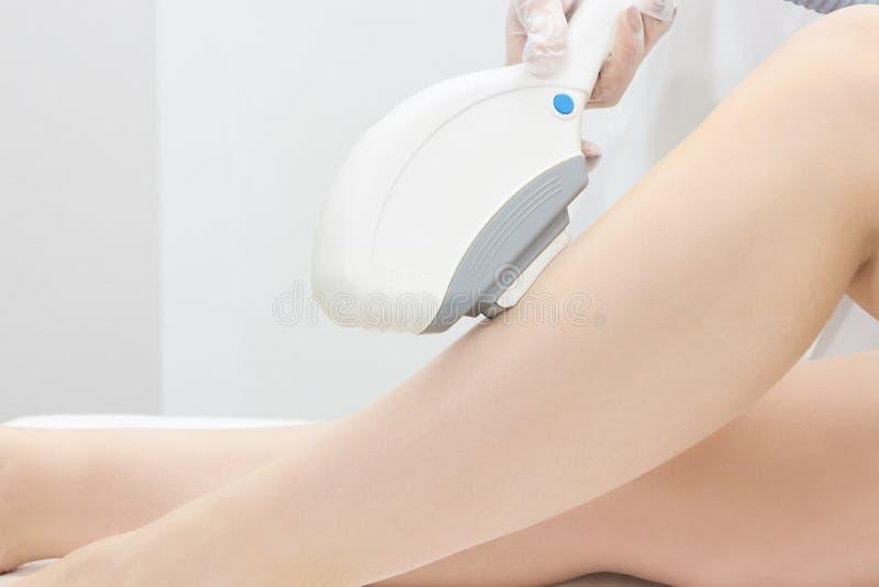 Φωτεινό δέρμα Ιατρική διαδικασία σαλονιών Αφαίρεση τρίχας λέιζερ πόδια θηλυκών Γιατρός που κάνει το epilation στοκ εικόνες