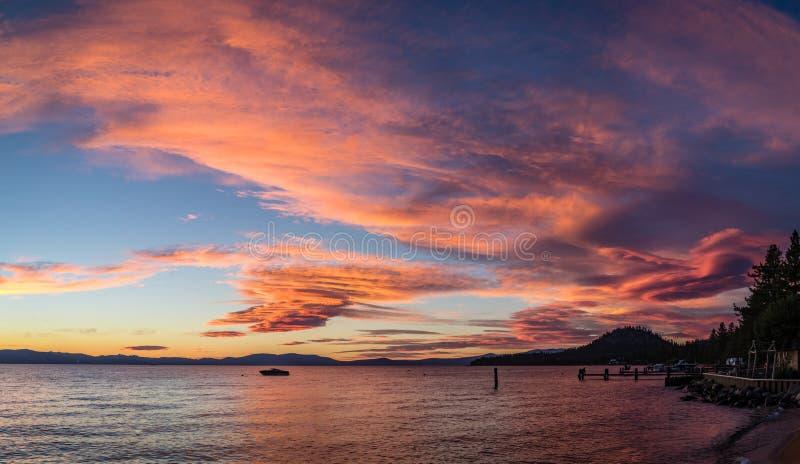 Φωτεινό ρόδινο, πορτοκαλί και μπλε ηλιοβασίλεμα με μια βάρκα στη μέση και μια αποβάθρα στη δεξιά γωνία που στέκεται στην όχθη της στοκ φωτογραφία με δικαίωμα ελεύθερης χρήσης