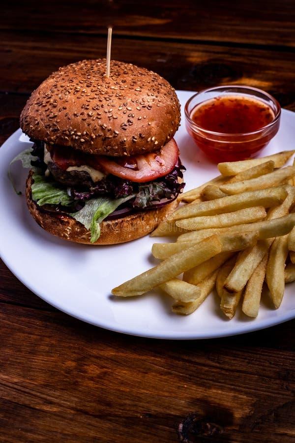 Χάμπουργκερ και τηγανητά που φωτογραφίζονται σε ένα άσπρο πιάτο που είναι σε έναν μαύρο ξύλινο πίνακα στοκ εικόνες