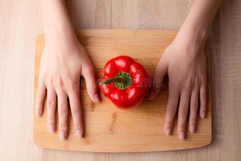 Χέρια γυναικών, μαχαίρι και ένα πιπέρι κουδουνιών στον ξύλινο τέμνοντα πίνακα στοκ εικόνες
