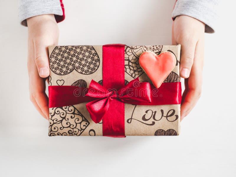 Χέρια ενός γονέα και ενός παιδιού, κιβώτιο με ένα δώρο στοκ εικόνες
