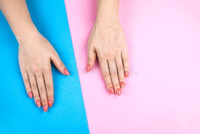 Χέρια της καλής νέας γυναίκας στο χρωματισμένο υπόβαθρο στοκ εικόνα με δικαίωμα ελεύθερης χρήσης