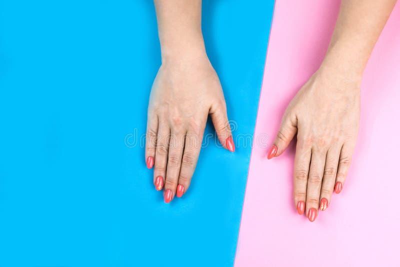 Χέρια της καλής νέας γυναίκας στο χρωματισμένο υπόβαθρο στοκ εικόνες