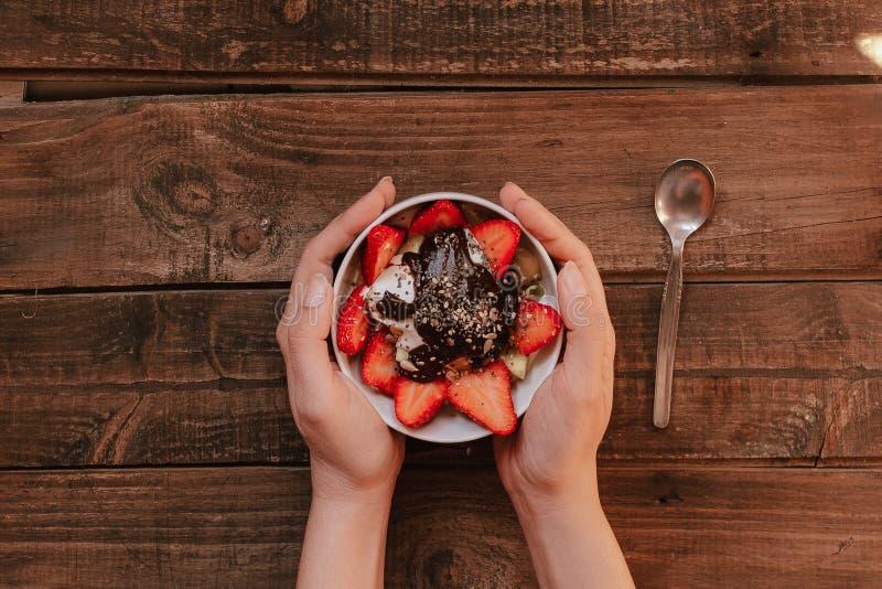 Χέρια που κρατούν τις φράουλες με τους σπόρους ηλίανθων chia σπόρων κολοκύθας σοκολάτας γιαουρτιού και το μήλο σε ένα άσπρο κύπελ στοκ φωτογραφίες με δικαίωμα ελεύθερης χρήσης