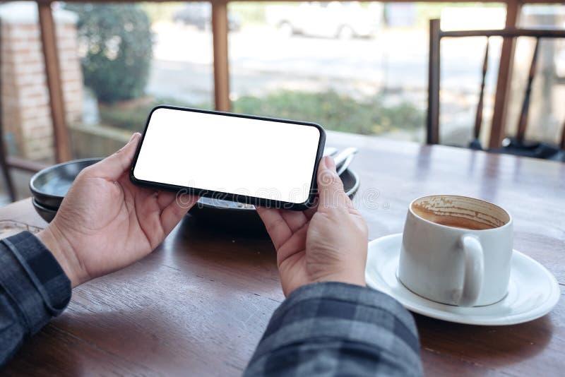 Χέρια που κρατούν το μαύρο κινητό τηλέφωνο με την κενή οθόνη υπολογιστών γραφείου οριζόντια με το φλυτζάνι καφέ στον πίνακα στοκ φωτογραφία με δικαίωμα ελεύθερης χρήσης