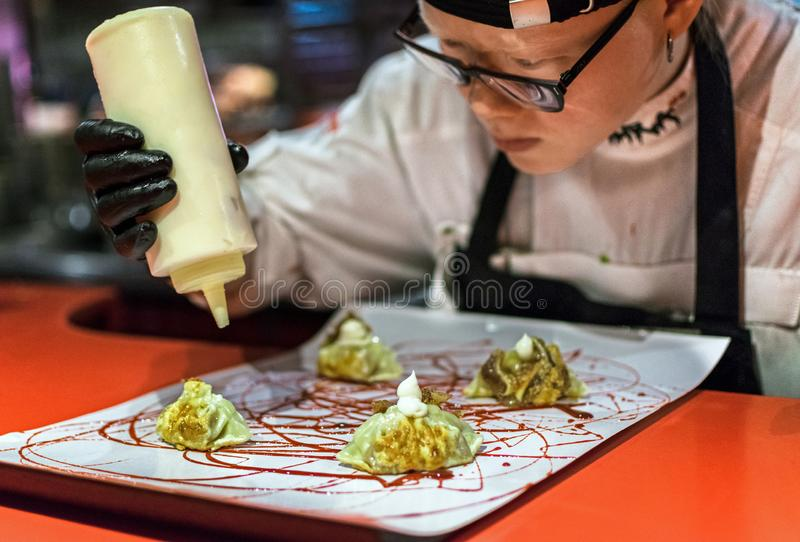 Χέρια που μαγειρεύουν το γαστρονομικό πιάτο Μπουλέττες Pekinese του χοίρου του αυτιού που εξυπηρετούνται με τη σάλτσα hoisin και στοκ εικόνες