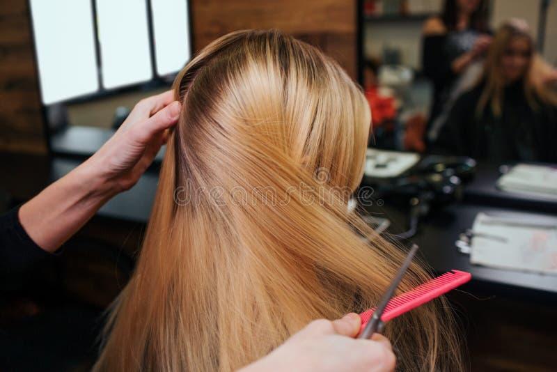 Χέρια Hairstylist που κτενίζουν την ξανθή τρίχα πριν από τις διαδικασίες προσοχής τρίχας στο σαλόνι ομορφιάς στοκ εικόνες με δικαίωμα ελεύθερης χρήσης