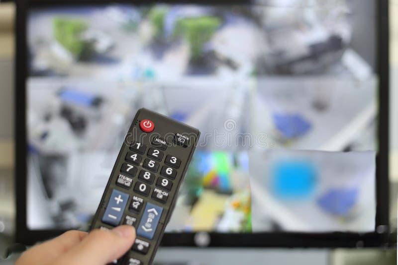Χέρι - κρατημένος τηλεχειρισμός για το CCTV ή τηλεόραση κλειστού κυκλώματος μπροστά από το υπόβαθρο οθόνης οργάνων ελέγχου θαμπάδ στοκ εικόνα με δικαίωμα ελεύθερης χρήσης