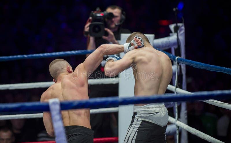 Χέρι λακτίσματος μαχητών μάχης MMA στο κεφάλι στοκ εικόνα