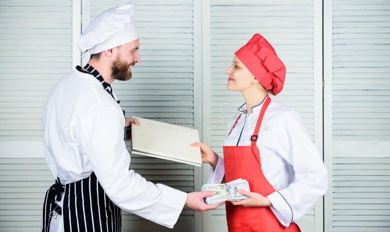 χέρι μετρητών Κύριο βιβλίο απολογισμού μαγείρων και εκμετάλλευσης αρωγών και χρήματα μετρητών Αρωγός μαγείρων που δίνει το μαγειρ στοκ εικόνα