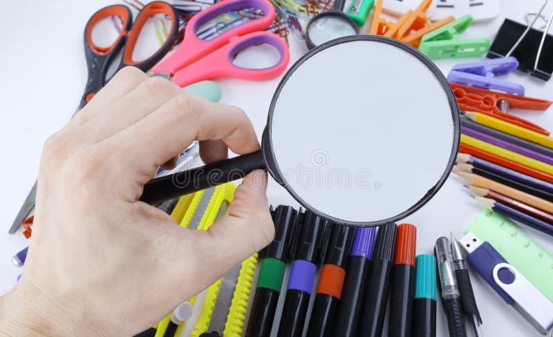 Χέρι με την ενίσχυση - γυαλί πέρα από τις σχολικές προμήθειες Φωτογραφία με το διάστημα αντιγράφων στοκ εικόνα