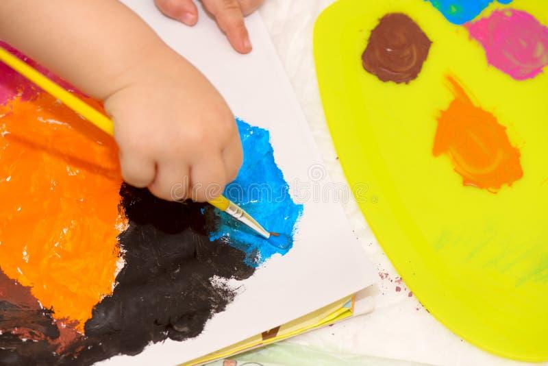 Χέρι παιδιού που κρατά ένα πινέλο και μια ζωγραφική στοκ φωτογραφία με δικαίωμα ελεύθερης χρήσης