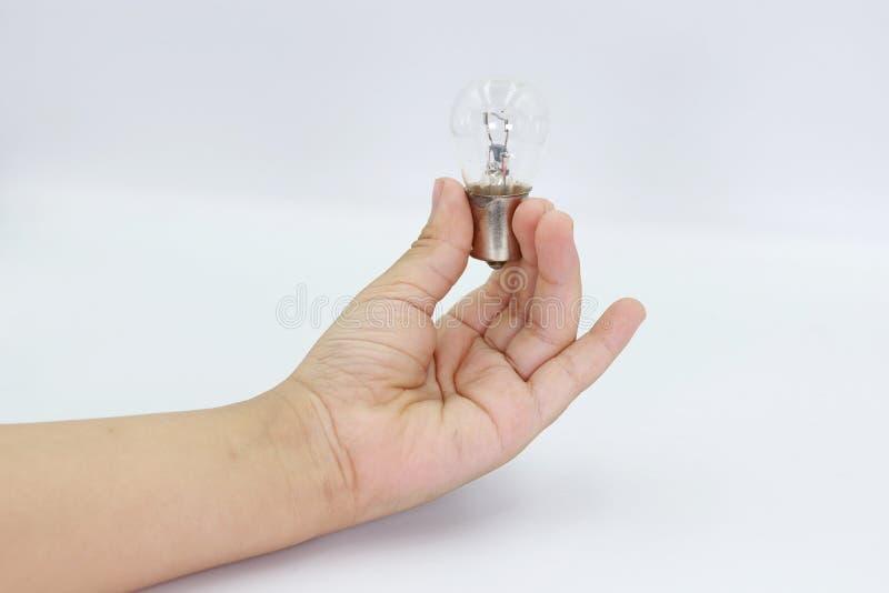 Χέρι παιδιών που κρατά μια λάμπα φωτός απομονωμένη στο άσπρο υπόβαθρο στοκ εικόνες