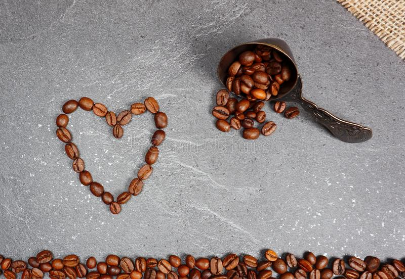 Χαλαρό τίμιο εμπόριο φασολιών καφέ με το κουτάλι και καρδιά στο υπόβαθρο κουζινών worktop στοκ εικόνα