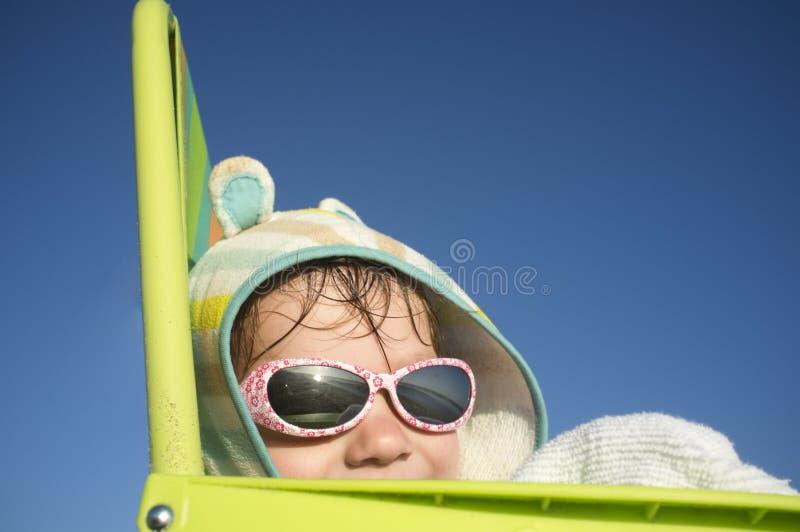 Χαμογελώντας 3 έτη συνεδρίασης αγοράκι πέρα από την καρέκλα παραλιών στοκ φωτογραφία με δικαίωμα ελεύθερης χρήσης