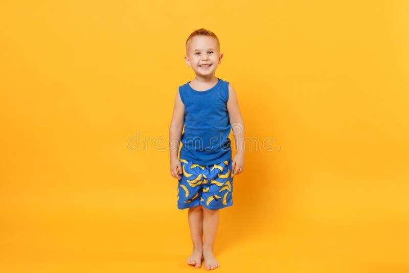 Χαμογελώντας αγόρι 3-4 παιδιών διασκέδασης χρονών που φορά τα μπλε θερινά ενδύματα παραλιών που απομονώνονται στο φωτεινό κίτρινο στοκ εικόνες