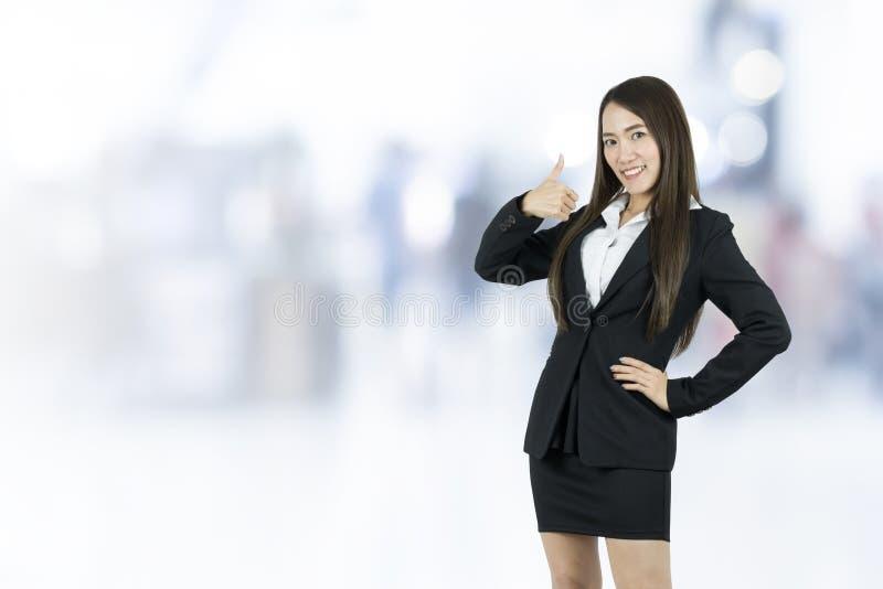 Χαμογελώντας ασιατική νέα επιχειρησιακή γυναίκα με τον αντίχειρα επάνω στοκ εικόνα