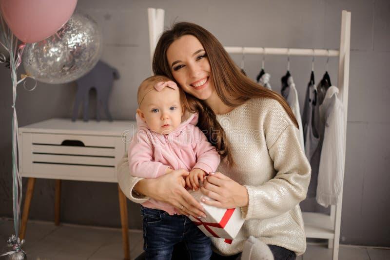 Χαμογελώντας γυναίκα και αυτή λίγη κόρη που κρατά ένα παρόν στοκ φωτογραφίες με δικαίωμα ελεύθερης χρήσης