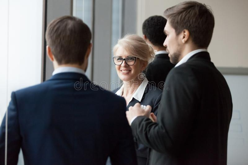 Χαμογελώντας επιχειρηματίας που απολαμβάνει τη φιλική συζήτηση με τα αρσενικά συνάδελφοι ή συνεργάτες στοκ εικόνα με δικαίωμα ελεύθερης χρήσης