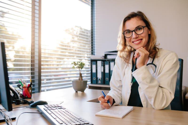 Χαμογελώντας θηλυκός γιατρός που κάθεται το γραφείο γραφείων της στοκ εικόνες με δικαίωμα ελεύθερης χρήσης