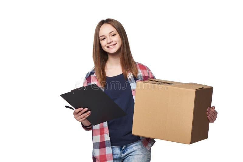 Χαμογελώντας κουτί από χαρτόνι και έγγραφο εκμετάλλευσης γυναικών που υπογράφουν το φύλλο στοκ φωτογραφία