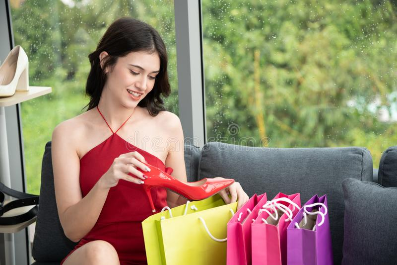 Χαμογελώντας νέα γυναίκα και μεγάλη ευχαρίστηση που κρατούν τα κόκκινα υψηλά παπούτσια τακουνιών σε ένα κατάστημα στοκ φωτογραφίες