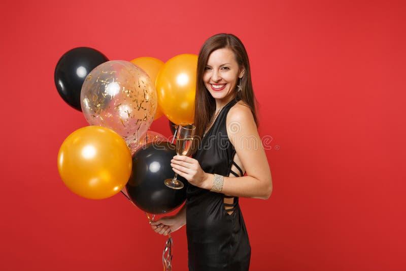 Χαμογελώντας νέα γυναίκα στο μαύρο εορτασμό φορεμάτων, κρατώντας το ποτήρι των μπαλονιών σαμπάνιας και αέρα που απομονώνονται στο στοκ εικόνα με δικαίωμα ελεύθερης χρήσης