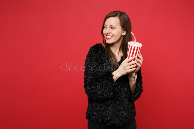 Χαμογελώντας νέα γυναίκα στο μαύρο πουλόβερ γουνών που κοιτάζει κατά μέρος, κρατώντας το πλαστικό φλυτζάνι της κόλας ή της σόδας  στοκ φωτογραφίες