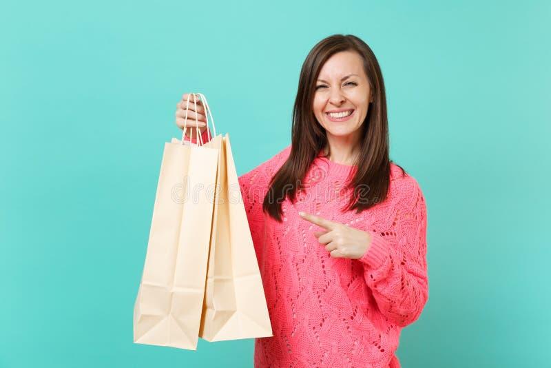 Χαμογελώντας νέα γυναίκα στο πλεκτό ρόδινο πουλόβερ που δείχνει το αντίχειρα στις τσάντες συσκευασιών με τις αγορές μετά από να ψ στοκ φωτογραφία με δικαίωμα ελεύθερης χρήσης
