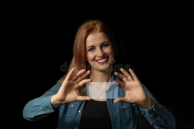 Χαμογελώντας νέα γυναίκα που κρατά ένα κενό διαφανές ορθογώνιο στοκ εικόνα