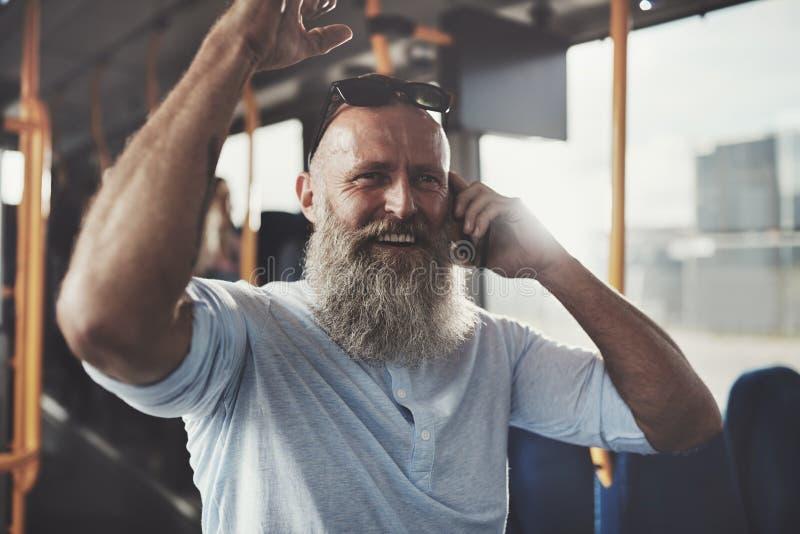 Χαμογελώντας ώριμο άτομο που οδηγά ένα λεωφορείο που μιλά στο κινητό τηλέφωνο του στοκ φωτογραφία