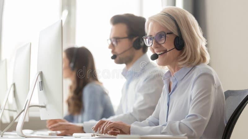 Χαμογελώντας παλαιός θηλυκός πράκτορας τηλεφωνικών κέντρων στο συμβουλευτικό πελάτη κασκών στοκ εικόνες