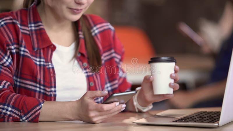 Χαμόγελο των χιλιετών φωτογραφιών εξέτασης γυναικών στο smartphone, κοινωνικά δίκτυα, συσκευές στοκ φωτογραφία με δικαίωμα ελεύθερης χρήσης