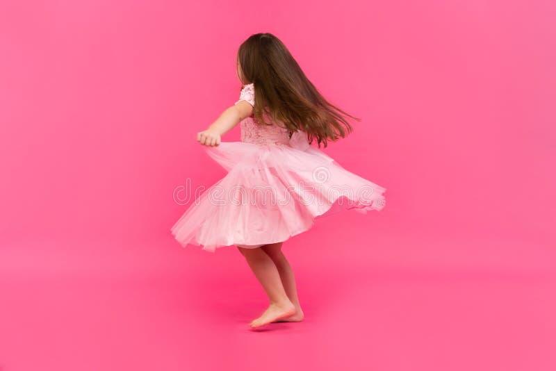 Χαριτωμένα όνειρα μικρών κοριτσιών να γίνει ένα ballerina χορεύοντας κορίτσι ελάχ&io Βλαστός στούντιο πέρα από το ρόδινο υπόβαθρο στοκ εικόνες