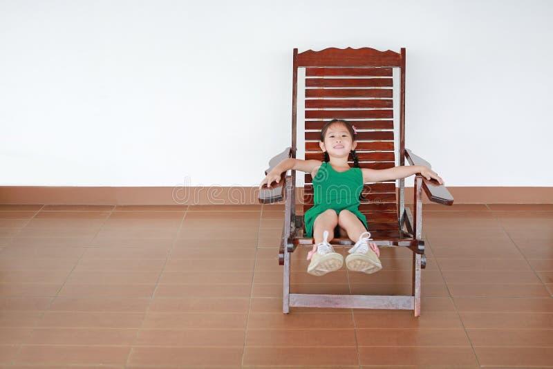 Χαριτωμένος λίγο ασιατικό κορίτσι παιδιών που βρίσκεται στην ταϊλανδική ξύλινη παραδοσιακή καρέκλα στοκ εικόνες