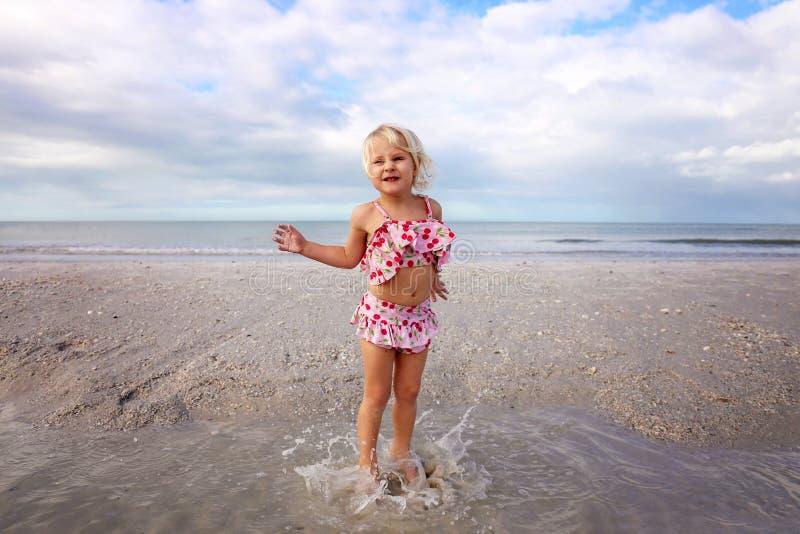 Χαριτωμένος λίγο παιδί που καταβρέχει και που παίζει στο νερό στην παραλία από τον ωκεανό στοκ εικόνα