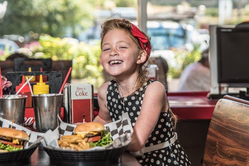 Χαριτωμένο κορίτσι που πίνει ένα κόκα κόλα ένα εστιατόριο ύφους της δεκαετίας του '50 με τα γυαλιά ηλίου στοκ φωτογραφία με δικαίωμα ελεύθερης χρήσης