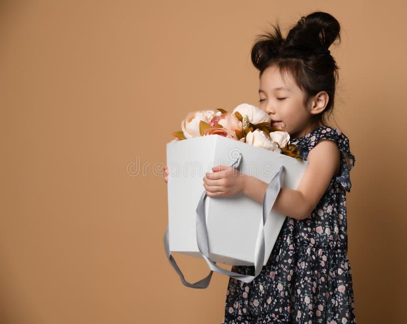 Χαριτωμένο λίγο ασιατικό κορίτσι στο όμορφο φόρεμα άνοιξη κρατά ένα μεγάλο καλάθι μεγάλο άσπρο pion λουλουδιών και το μυρίζει στοκ φωτογραφία