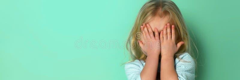 Χαριτωμένο λίγο ξανθό κορίτσι που καλύπτει το πρόσωπό του για το peekaboo παιχνιδιού, δορά - και - επιδιώκει στοκ εικόνες