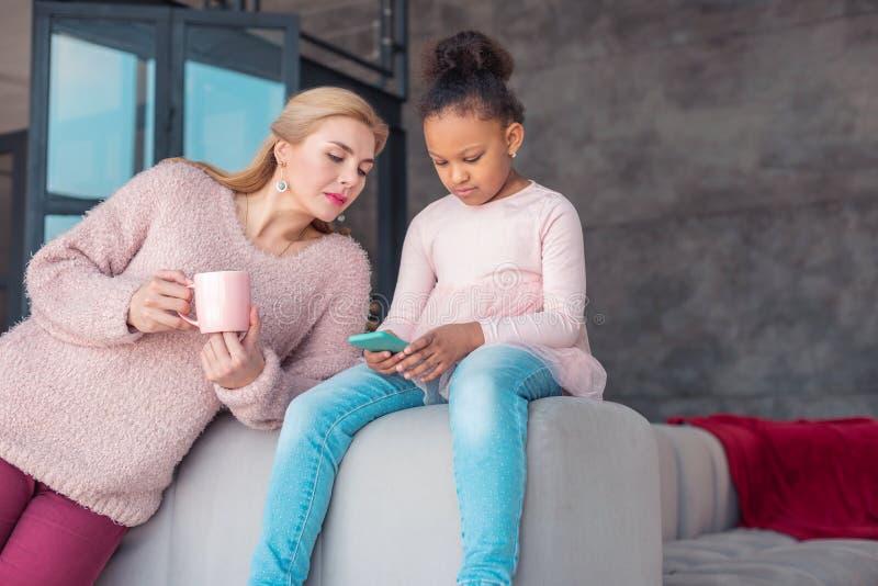 Χαριτωμένο μικρό κορίτσι που χρησιμοποιεί την μπλε συνεδρίαση smartphone της κοντά στη μητέρα στοκ φωτογραφίες