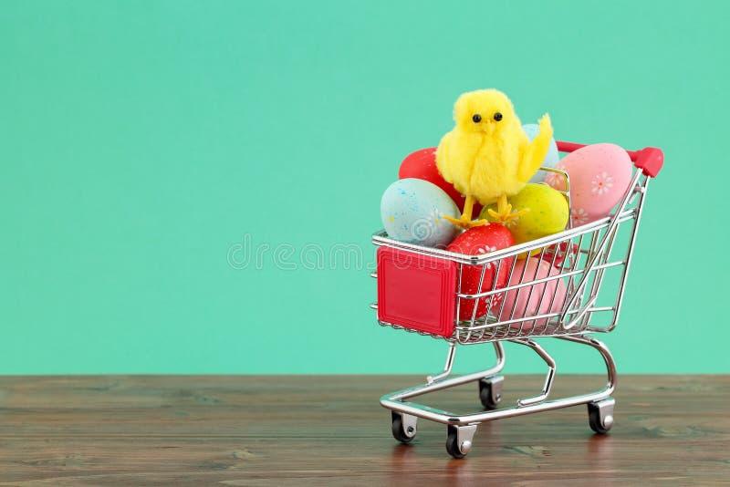 Χαριτωμένο διακοσμητικό κοτόπουλο σε έναν σωρό των ζωηρόχρωμων χρωματισμένων αυγών σε ένα κάρρο αγορών στο τυρκουάζ κλίμα με το δ στοκ εικόνες με δικαίωμα ελεύθερης χρήσης