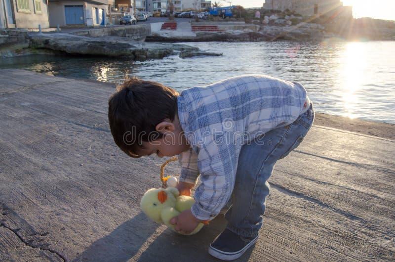 Χαριτωμένο χρονών παιχνίδι μικρών παιδιών δύο με το μικρά παιχνίδι και το καλάθι κοτόπουλου με δύο αυγά Πάσχας στο έγγραφο θάλασσ στοκ φωτογραφίες