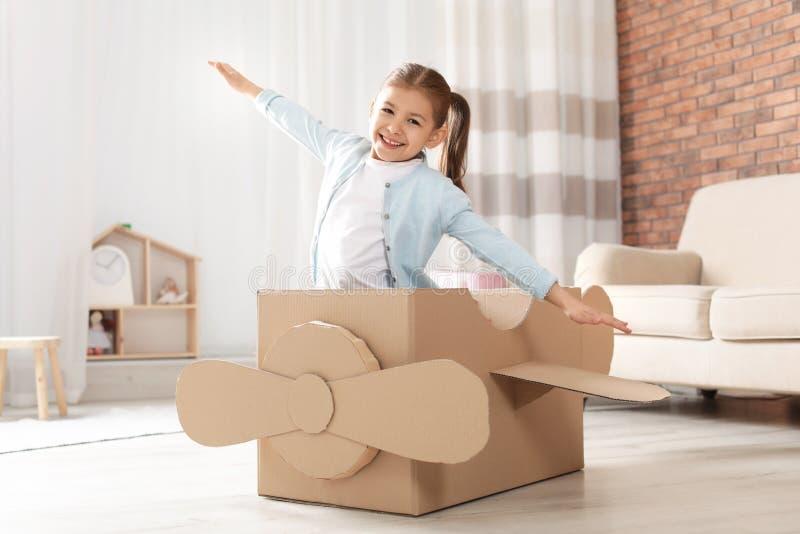 Χαριτωμένο παιχνίδι μικρών κοριτσιών με το αεροπλάνο χαρτονιού στοκ φωτογραφία με δικαίωμα ελεύθερης χρήσης