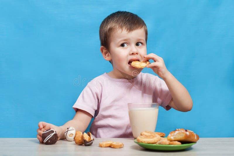 Χαριτωμένο πόσιμο γάλα μικρών παιδιών και κατανάλωση των μπισκότων στοκ φωτογραφίες