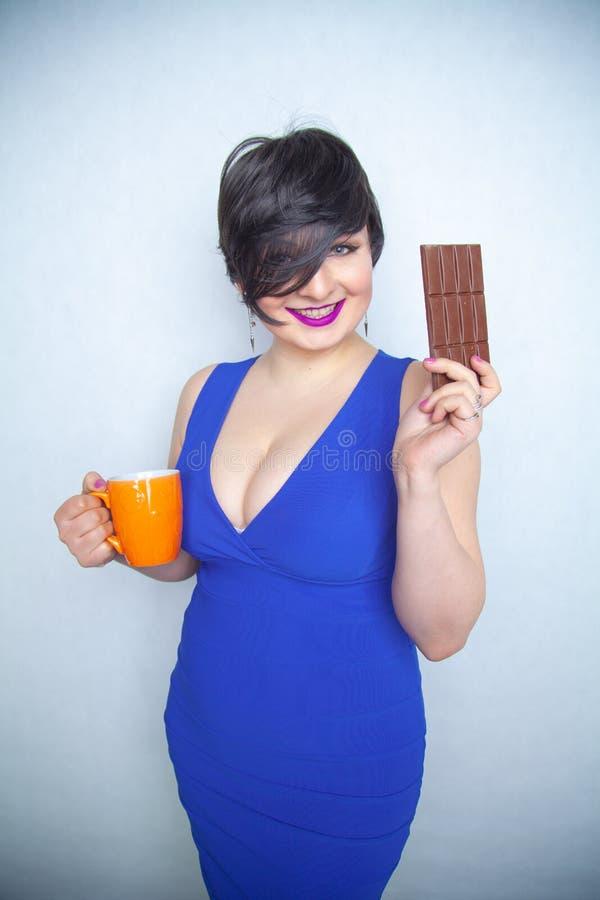 Χαριτωμένο chubby κορίτσι με την κοντή μαύρη τρίχα σε ένα μπλε φόρεμα που κρατά έναν φραγμό σοκολάτας και ένα φλυτζάνι στα χέρια  στοκ εικόνες
